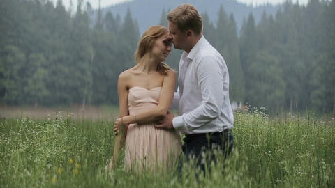 Charming couple in love hugging in the grass on the mountains background Live Action