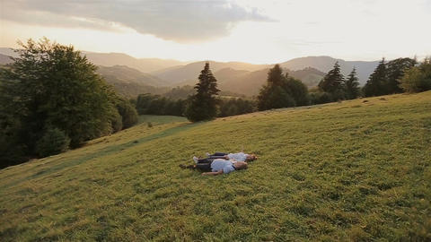 Charming couple in love and lie on the grass in the mountains on sunset Footage