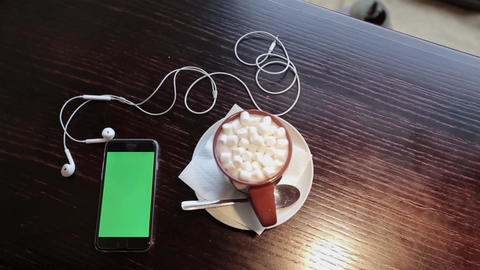 Cup of coffe with marshmellou and cellphone with green in cafe Footage