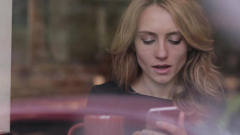 Woman using app on smartphone in cafe drinking coffee smiling and texting on mob Footage