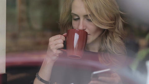 Businesswoman with smartphone drinking coffee in cafe Footage