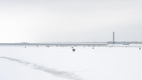 Two winter fishermen walking toward a large group of anglers Footage