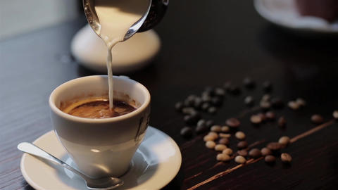 Pouring milk into coffee in cafe Footage