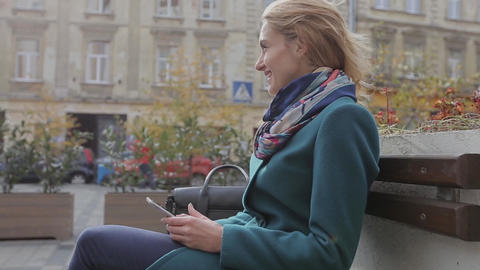 Attractive young woman using her touch screen mobile cell phone and smiling to h Footage