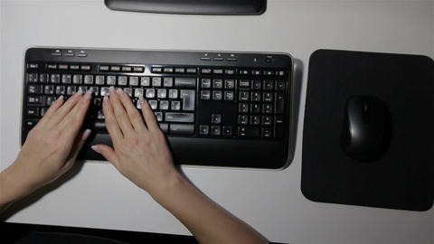 Young woman typing on a PC keyboard