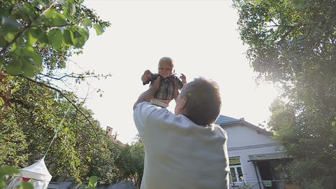 Grandfather playing with baby in backyard Footage