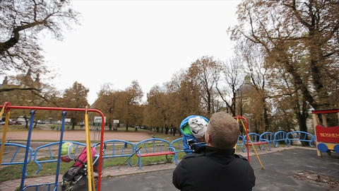 Father playing with young son at a playground.father throws the son upwards Footage