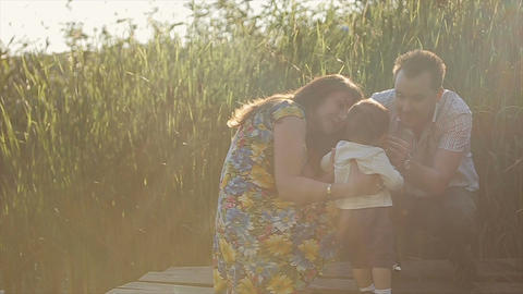 Happy family have fun in backyard at lake. Little baby have fun with his parents Footage