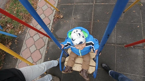 Adorable baby boy with big beautiful eyes having fun on a swing ride at a playgr Footage
