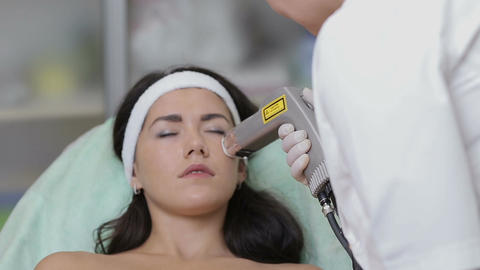 Woman with closed eyes getting photo rejuvenation procedure in a beauty salon.Co Footage