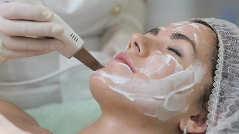 Woman cleaning skin on beautiful client face in beauty salon Footage