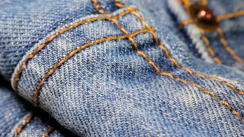 Extreme close-up tilt shot of the dark blue denim fabric of jeans with bright ye