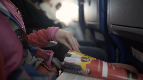 Female passenger reading airline magazine during flight on board of airplane Footage