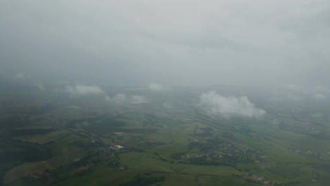 View from plane at fog and clouds flying above green landscape, weather forecast Footage