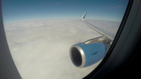 Plane flying above thick white clouds in tranquil blue sky, vacation travel Live Action