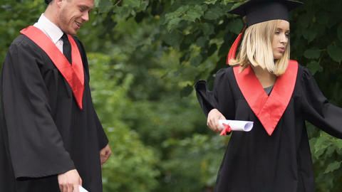 Funny graduates in academic dresses dancing and singing at park near university Footage
