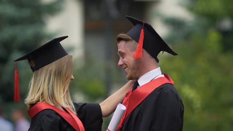 Two friends hugging at graduation ceremony, young people celebrating achievement Footage