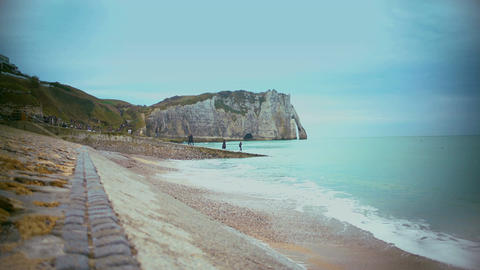 Tourists walking on coast near famous Etretat cliffs and enjoying beautiful view Footage