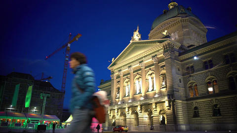 Evening city life, Swiss Parliament building in Bern and illuminated ice rink Footage