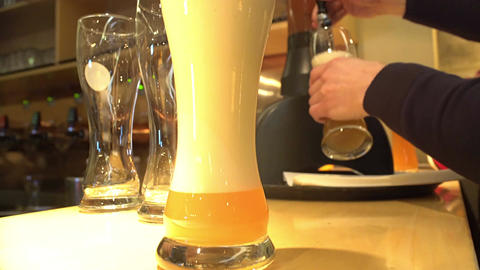 Barman pouring foamy beer into glasses, brewing business, catering service Footage