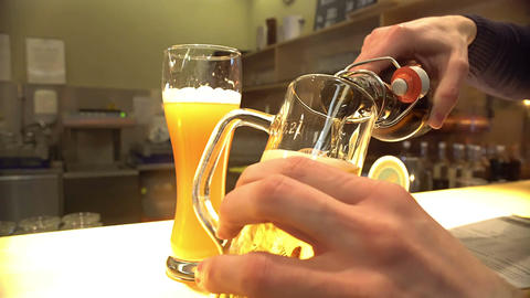 Male hands pouring bottled alcohol into glass at pub, beer brewing industry Footage