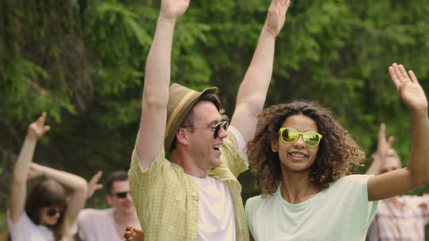Cheerful men and women waving hands up in air, laughing and enjoying happy life Footage