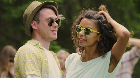 Slowmotion of young couple in sunglasses smiling to camera, happy people hugging Footage