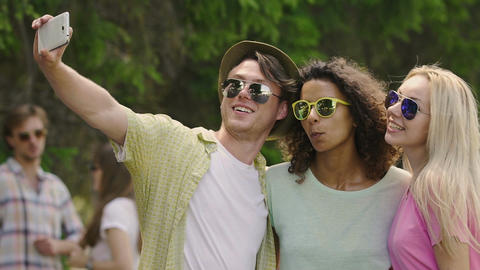 Classmates pulling funny faces and taking selfie at outdoor music festival Footage