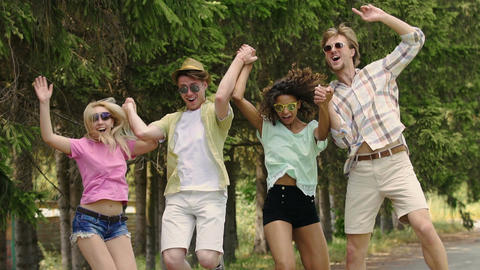 Four multiracial friends jumping together in park at open-air music festival Footage