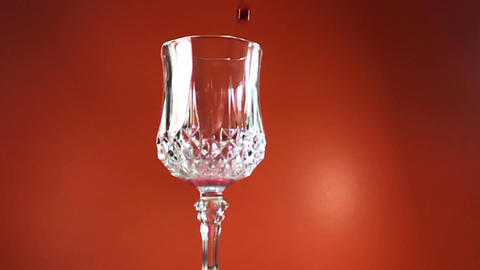 Red Wine Pouring into Glass. orange Background. Slow Motion