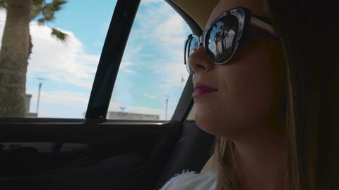 Nice woman in sunglasses enjoying view on beach through car window, taxi service Footage