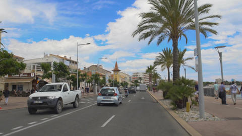 Car riding in resort city street, people walking on embankment, urban life Footage