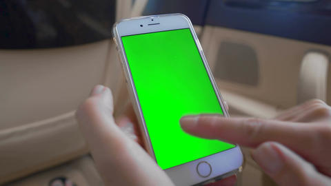 Female hands scrolling on smartphone with green screen, chroma key alpha channel Footage