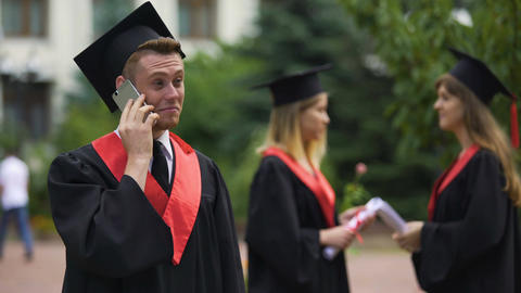 Happy male graduate receiving prestigious job offer, telephone conservation Live Action
