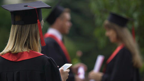 Female graduate texting on smartphone and relaxing after graduation ceremony Footage
