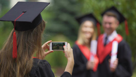 Young woman in academic dress taking photos of friends on cellphone, graduation Footage
