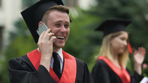 Male graduating student enjoying phone conversation and laughing cheerfully Footage