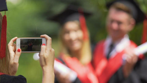 Young couple of university graduates hugging and posing for photo, thumbs-up Footage