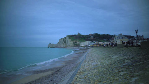 Evening promenade, people walking on embankment and enjoying weekend in Etretat Footage