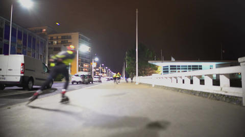 People roller skating in light reflecting vests at night, healthy lifestyle Footage