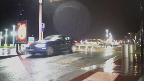 Rainy cold weather in town, lone car driving on the road, dim city lights Footage
