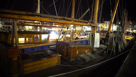 Panorama of wooden fishing boat parked in harbor, beautiful evening cityscape Footage
