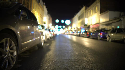 Many cars parked along illuminated street with stores, car theft protection Footage