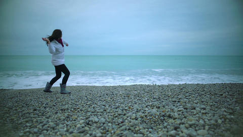 Beautiful girl throwing pebbles into sea and enjoying good view, splashing water Footage
