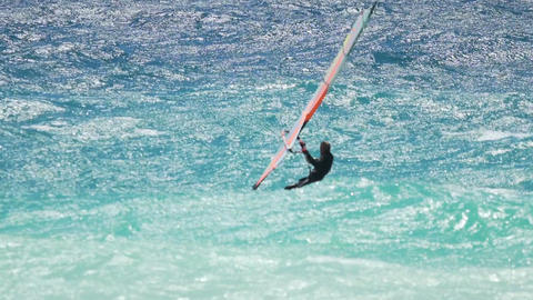 Windsurfer gliding on waves on a sunny summer day, professional sports, hobby Footage