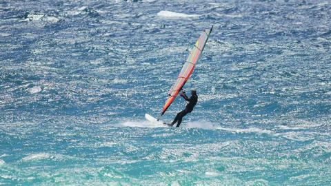 Male windsurfing on waves professionally, interesting and risky hobby, lifestyle Live Action