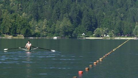 Male athlete rowing on tranquil lake, professional boat racing, competition Live Action
