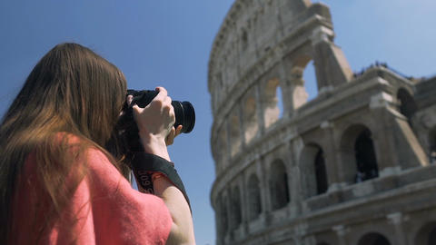 Female tourist using camera to take photo of Coliseum, enjoying hobby at leisure Live Action