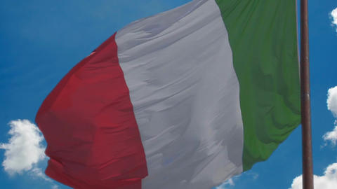 Flag of Italy waving in wind proudly, blue sky background, national symbol Footage