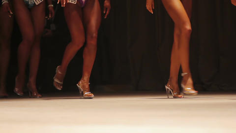 Fit tanned legs of beautiful fitness models walking on stage in high heel shoes Live Action